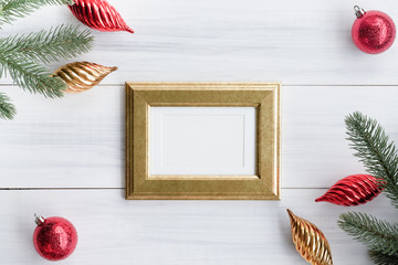 Top view of blank golden picture frame with red decoration ball, gold christmasand pine brance on white wood table top,Flat lay luxury holiday celebration still life,mock up for adding text,copy space