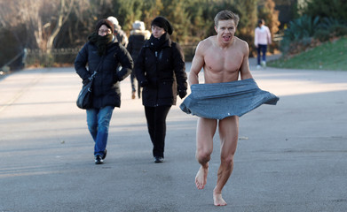 A swimmer dresses after emerging from an open-air swim in near freezing temperatures in the Serpentine lake in Hyde Park, London