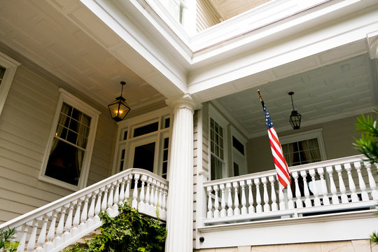 american flag outside white wooden american home porch in charleston south carolina