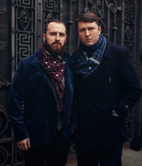 a two handsome brutal man in a jacket and scarf stands near a metal gate