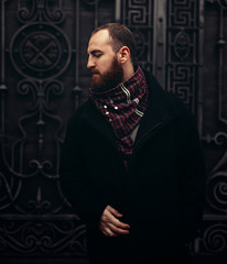 a handsome bearded brutal man in a jacket and scarf stands near a metal gate