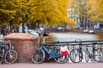 Bike on the bridge in Amsterdam, Netherlands. Beautiful view of canals in autumn