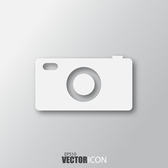Camera icon in white style with shadow isolated on grey background.