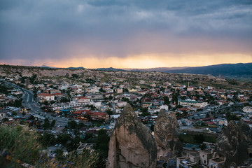 Top view. A small authentic city called Goreme in Cappadocia in Turkey in the evening. Dramatic night sky, sunset.