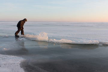 Man in warm clothes walking through a crack on thin ice on a a frozen river , Ob reservoir, Siberia, Russia