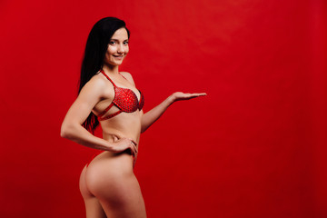 beautiful young girl fitness model stands on red background in sexy bra.