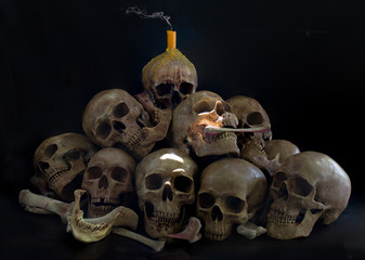 Pile of Skulls with candle with smoke on the head and bone on black background  and have light splash in dark room