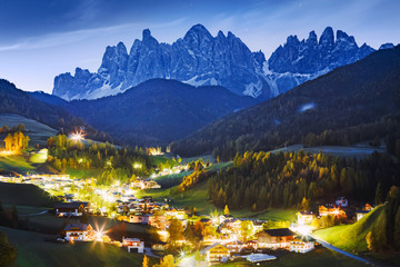 Wall Mural - Italy, Dolomite Alps. Fabulous night landscape of small scenic village  Santa Maddalena - Magdalena at alpine mountain ridge background. Lit scenic valley at twilight. Charming Autumn season in Alps.