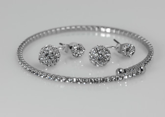 Diamond tennis bracelet with earrings on white reflection