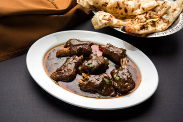 lamb shank or mutton or gosht paya or khoor curry served with indian bread or roti or naan