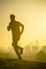 Moody sunrise silhouette of a jogger running on a green grass hillside in front of the misty morning city skyline of London, England