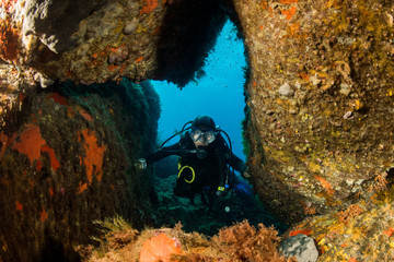 woman scuba diving over rocks in the Mediterranean Sea