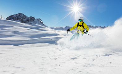 Young skier running downhill in beautiful Alpine landscape.