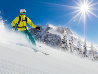 Skier on piste running downhill in Alpine landscape.