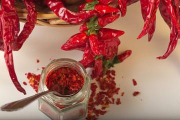 Peperoncino rosso piccante macinato nel vasetto di vetro, con peperoncini sani essiccati nel cesto.