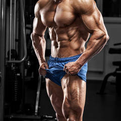Muscular man in gym, bodybuilder. Strong male naked torso abs, working out