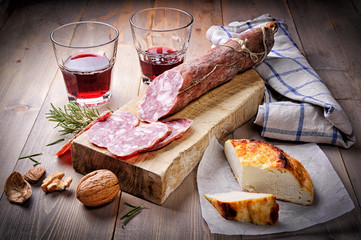 Salami, cheese and red wine on wood background
