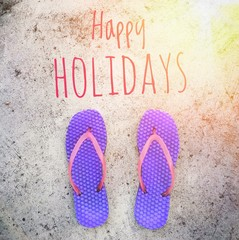 """Slippers / flip flops / shower sandals in purple and pink color on cement floor;  """"Happy Holidays"""" phrase with flare light Use as visual content in concepts of holiday, relaxation, vacation."""