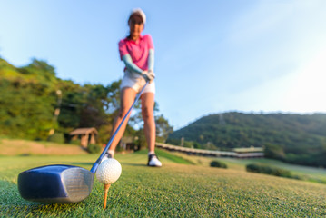 Close up of golf ball before a women tee off in the ground evening time.  Lifestyle Concept
