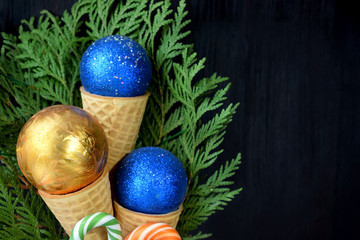 Christmas balls in waffle cones. Thuja branches in the background. Copy space