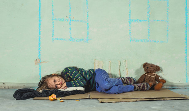 Homeless kid girl sleeping on the carboards.