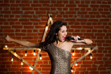 Young beautiful woman singing song over wooden star with bright lamps as background