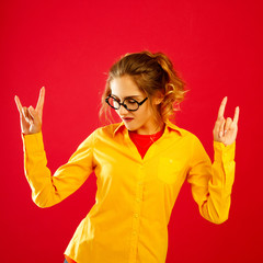 Young funny pretty woman with rock-n-roll gesture over red background