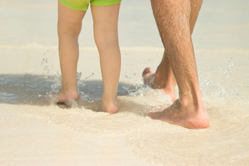 Dad and son are walking along the beach. Close-up of legs.