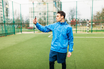 The guy is listening makes a selfie during a workout. A young man plays sports, runs on the football field. The guy works in the open, fresh air.