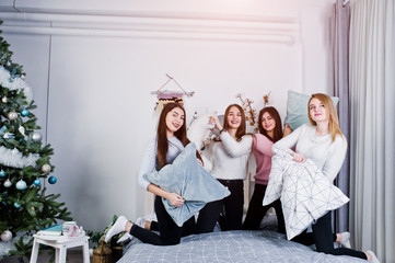 Four cute friends girls wear on warm sweaters and black pants on bed at new year decorated room on studio, play with pillows.