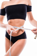 Woman with perfect body in black underwear measuring her waistline. Closeup of female with perfect slim body and torso. Healthy nutrition and weight losing concept.
