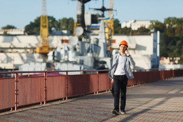 Handsome young unshaven successful business man in gray suit and protective construction orange helmet holding case, talking on mobile phone, walking in sea port against cargo ship, crane background