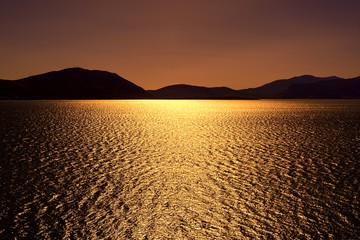 Dark bronze sunset with sun shimmering sun reflections on lake u