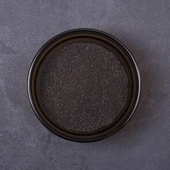 Black cumin powder in a bowl on a grey concrete background