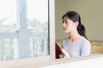 Asian beautiful young woman reading red book and sit side window. concept of education, learning, knowledge, information and big data.