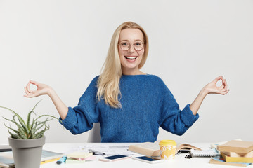 Positive carefree female office worker tries to relax after long hours of work, sits in lotus pose, meditates and concentrates, has happy expression, isolated over white background. Relaxed woman