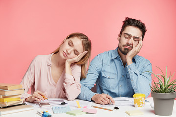Portrait tired crew of office workers sit at table, fall asleep after working long hours on preparing startup project, feel tiredness, isolated over pink background. People and overworking concept Wall mural