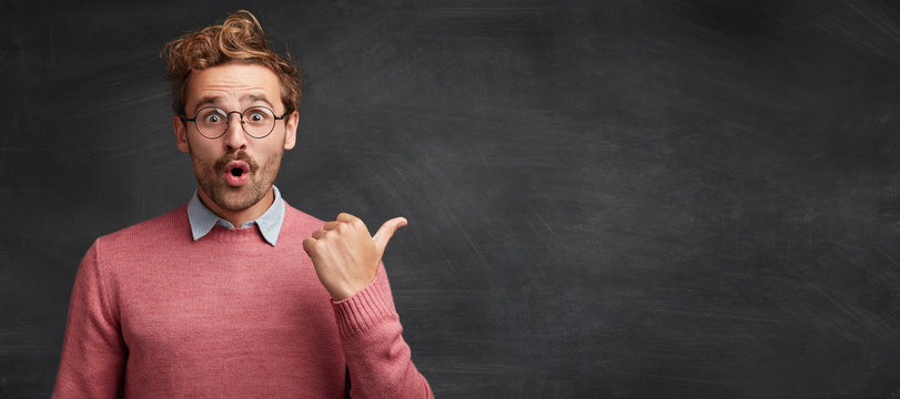 Horizontal shot of shocked male student with stylish hairdo, stares through spectacles, being surprised to indicate something at copy space for your promotional text or hearder. Advertising concept