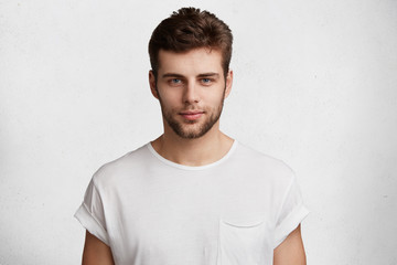 Serious confident young male student comes home after classes, dressed casually in white t shirt, waits for girlfriend, isolated over white background. People, youth, beauty, lifestyle concept