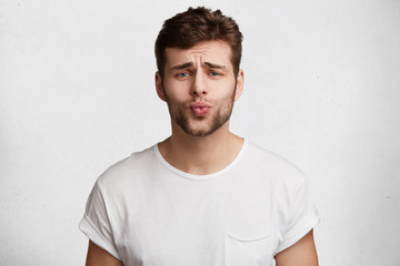 Horizontal portrait of bearded stylish young male rounds lips and has pleading expression, asks for forgiveness in her girlfriend as comes home late, isolated over white concrete background.