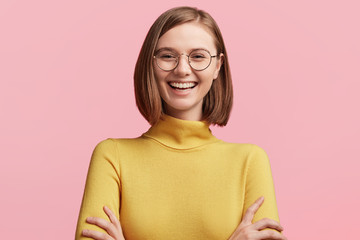Cheerful female student has fun during break in colleague, laughes at jokes of groupmates, keeps hands crossed, wears round optical glasses and yellow turtleneck sweater. Positive emotions concept