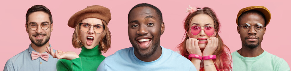 Horizontal portrait of five people express different emotions, stand in row next to each other, isolated over pink background. Dark skinned smiling male in centre and his friends or relatives
