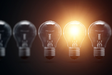 A series of electric light bulbs, only one glows, against a dark background. The concept of several attempts, one successful. A successful idea.