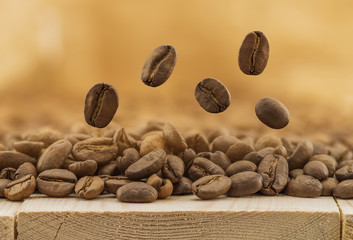 Flying fresh coffee beans on yellow blurred background with copy space. Coffee beans falling down
