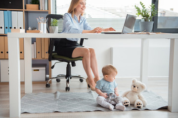 Happy woman typing in laptop while sitting at table. Full length serene baby playing with toys on floor in apartment. Profession and parent concept