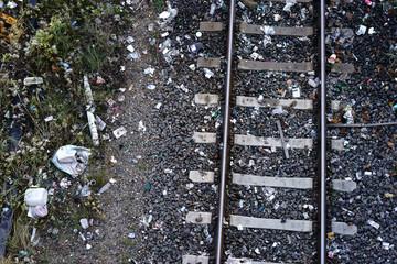 Müll auf den Gleisen  / Die Draufsicht auf ein Gleisbett mit Schienen und Schottersteinen sowie einer Menge Müll und Abfall.