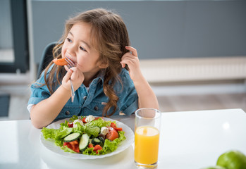 Dreamful asian girl is eating fresh tomato with appetite. She is sitting and looking aside playfully. Plate of salad and glass of juice on table. Copy space