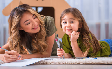 Portrait of happy mother and daughter entertaining on flooring at home. Girl is looking at camera with excitement and holding pencils. Woman is drawing and smiling