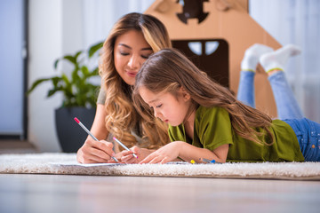 Joyful asian mother and daughter are drawing picture by pencils with interest. They are lying on soft flooring carpet at home