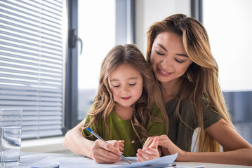 Cheerful asian woman is showing how to draw picture on paper to her little daughter. She is embracing her and smiling. Portrait